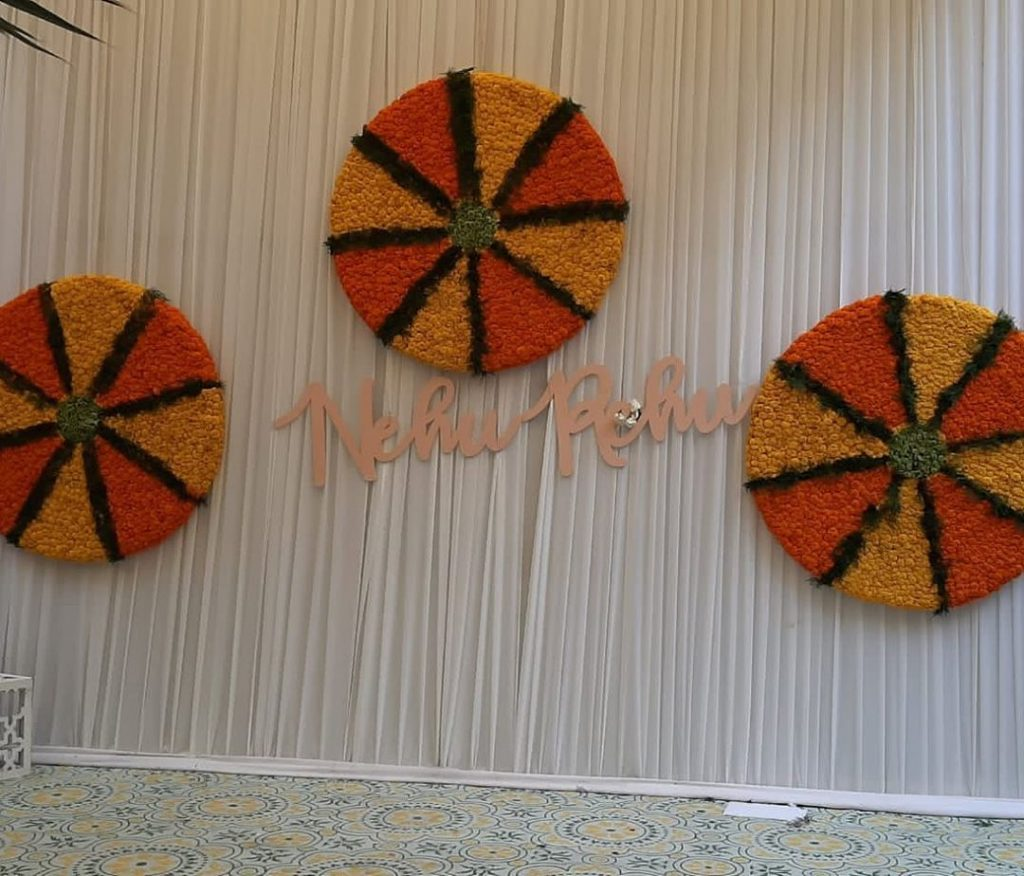 white drapes and circular mariigold floral wheel with pastel nehupreet text for haldi backdrop