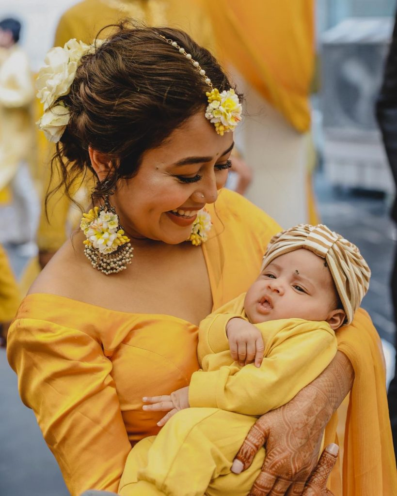 neha holding baby during haldi ceremony with yellow white floral haldi jewellery