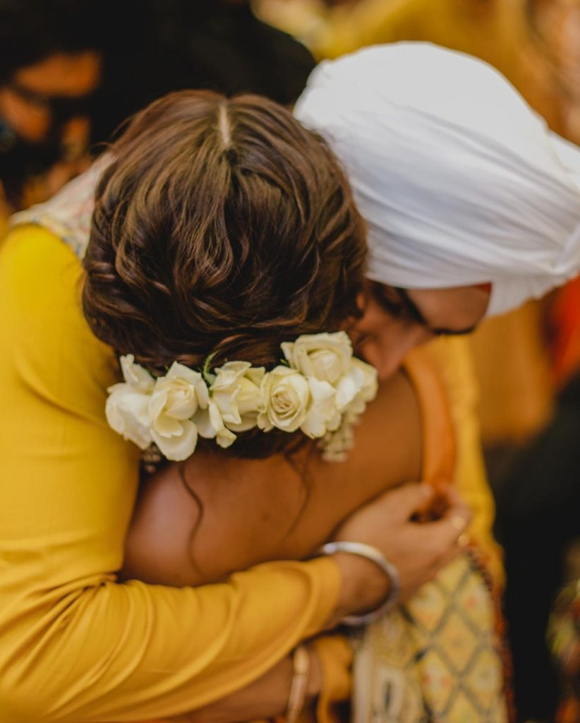 neha with floral hair bun hugging groom rohanpreet