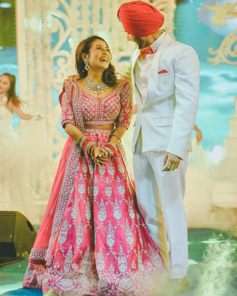 neha kakkar wearing hot pink silver embroidered anita dongre lehenga posing with rohanpreet in white tuxedo by TISA studio