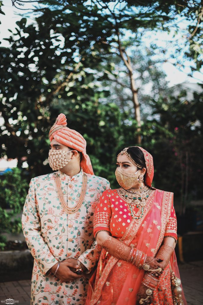 couple in coordinating pastel silk face masks with patterned zari embroidery