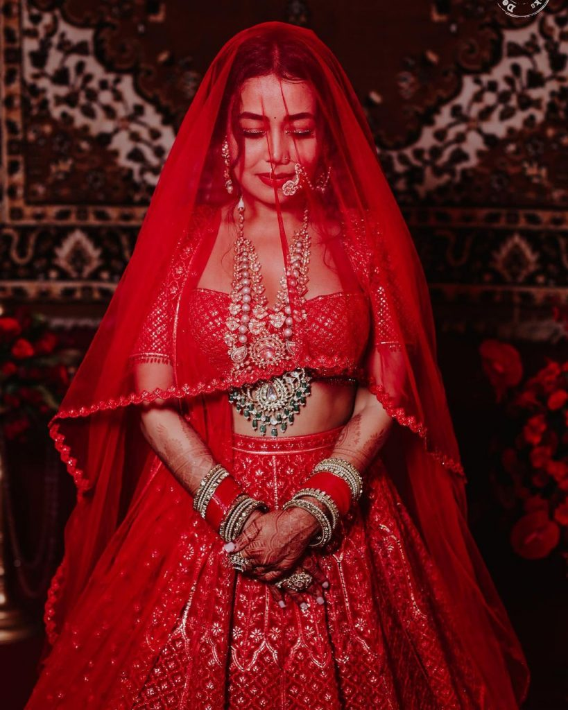red sheer neha kakkar bridal veil posing for wedding ceremony with rohanpreet