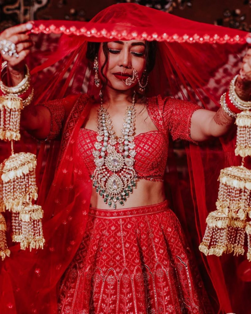 golden wedding kaleera and silver ethnic jewellery and red lehenga of neha kakkar wedding