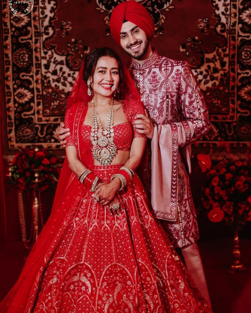 neha and rohanpreet in red themed colour coordinated wedding outfit
