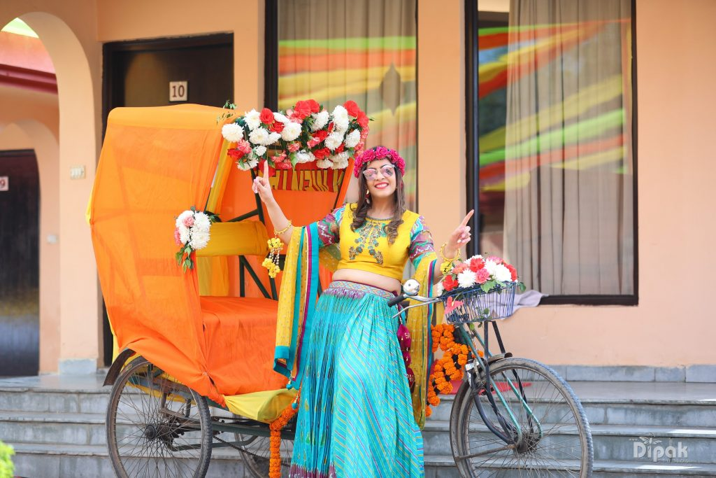 orange rickshaw with pastel flower decoration and posing indian bride