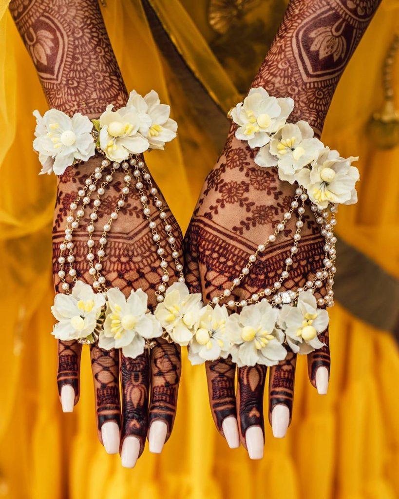 simplistic matt pink bridal nail art with white floral haldi jewellery