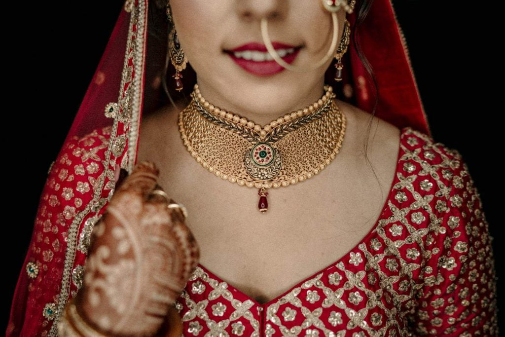 red bridal lehenga with gold jewellery