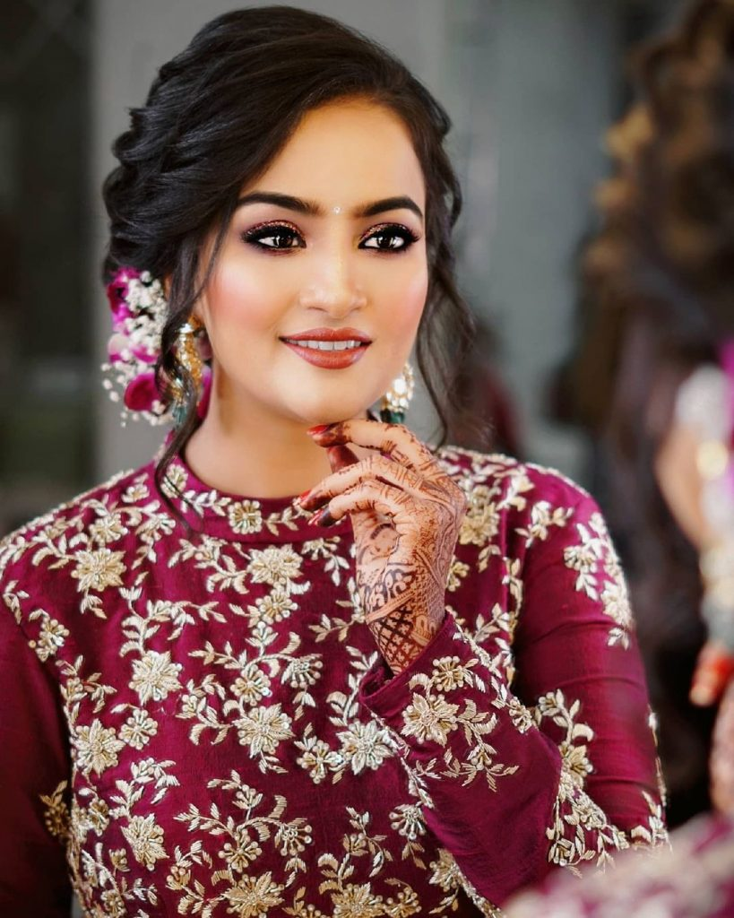 bridal hairstyle for round face shape with voluminous wavy front and earlocks