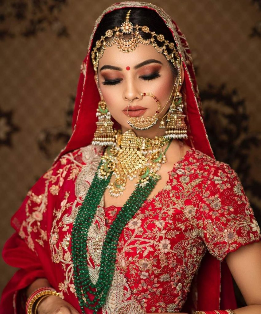 red lehenga with deep green and gold jewellery