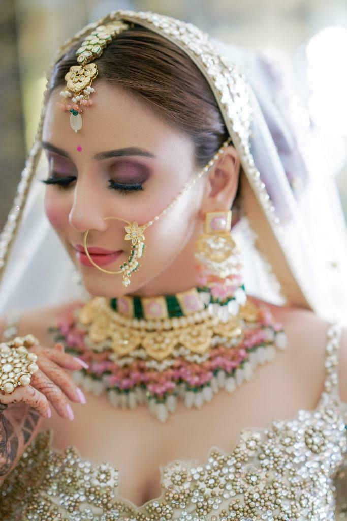 bride defining her eyelashes with mascara from her bridal makeup kit box