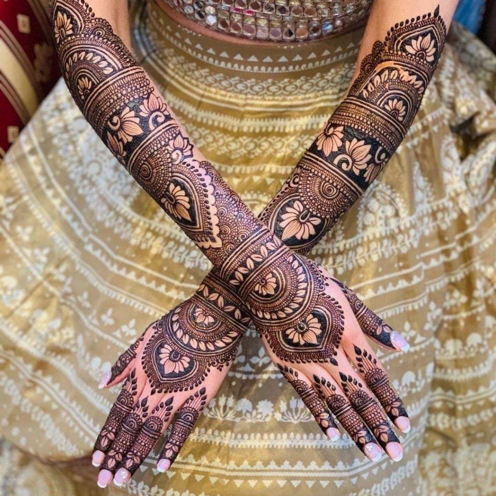 Exquisite full hand bridal mehndi design with lotus motifs