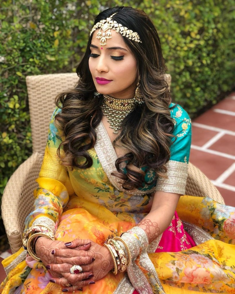 Wavy hairdo with matha patti for diamond face shape