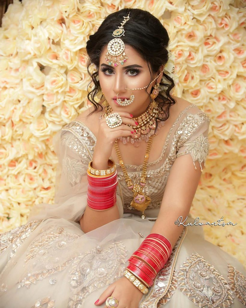 lehenga hairstyles for oval face with bridal up-do and stray hairlocks