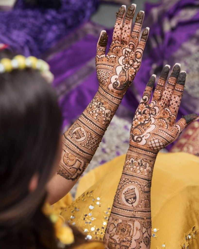 Intricate front hand bridal mehndi design with peacock and bell motifs