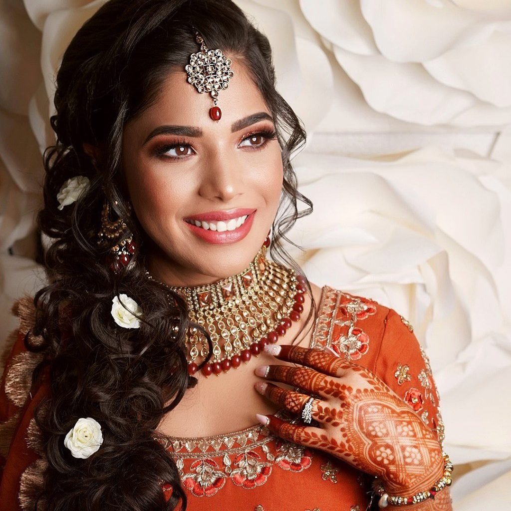 lehenga hairstyles for oval face with side swept messy braid