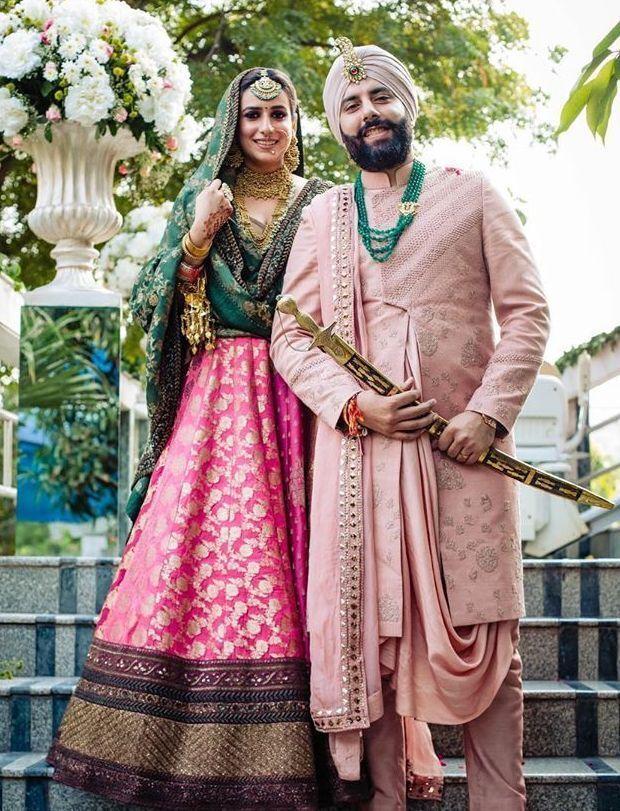 Sabyasachi couple with bride in rani pink lehenga and dark green choli