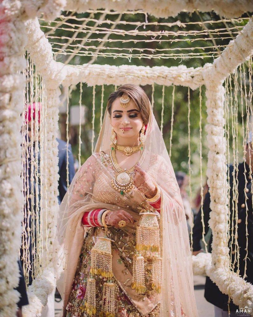 bride entering in a floral cage