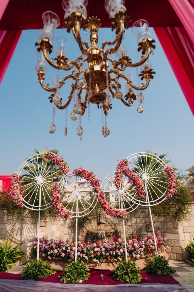 Floral outdoor Decor with pink flowers and cycle wheels for mehndi function