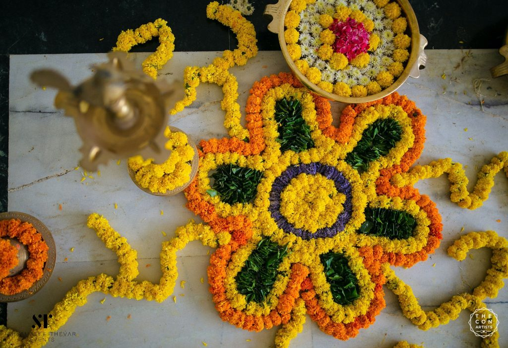 Indoor decoration with mogras, marigolds and vines accessorized with gold accessories