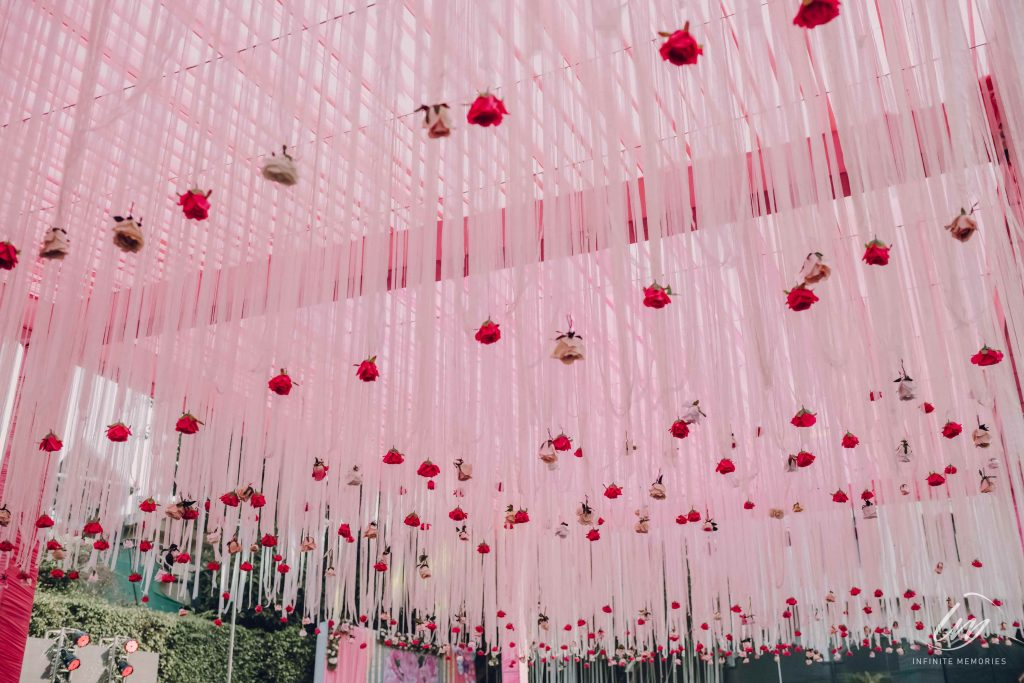 ceiling decorated in pink tones with roses for mehndi function