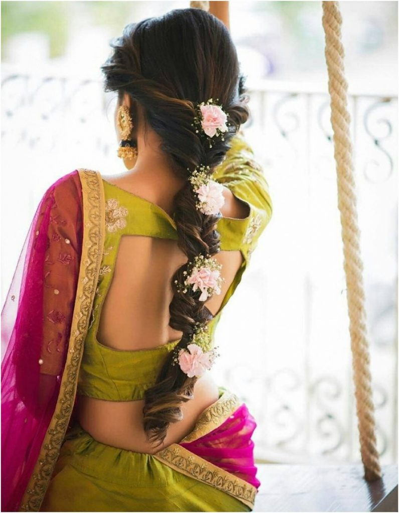 bride in a saree and her hair in braids