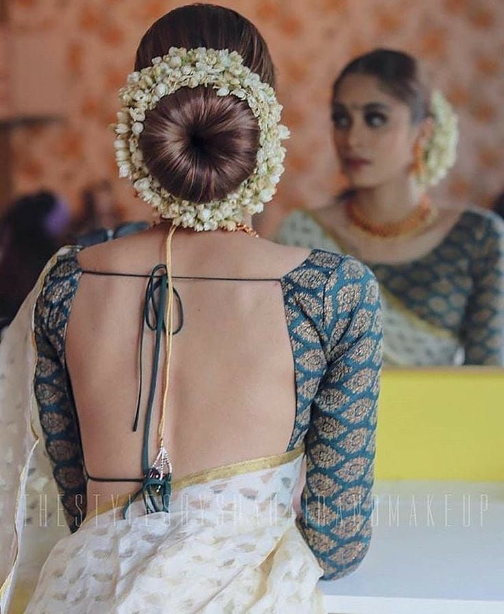 bride in a saree with her hair in a donut bun