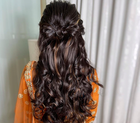bride in twisted hairstyle with open hair in soft curls
