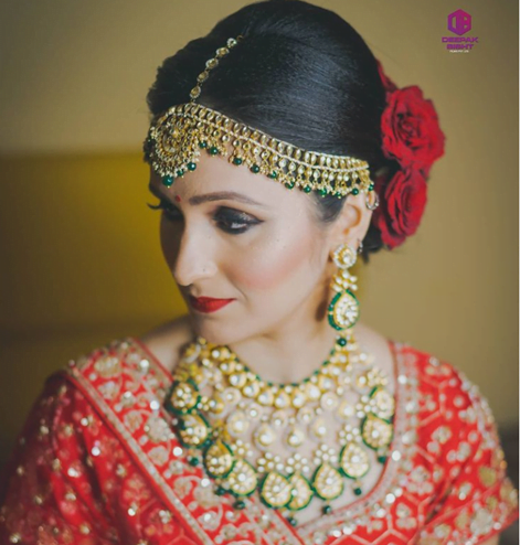 bride in red with hair adorned with red roses