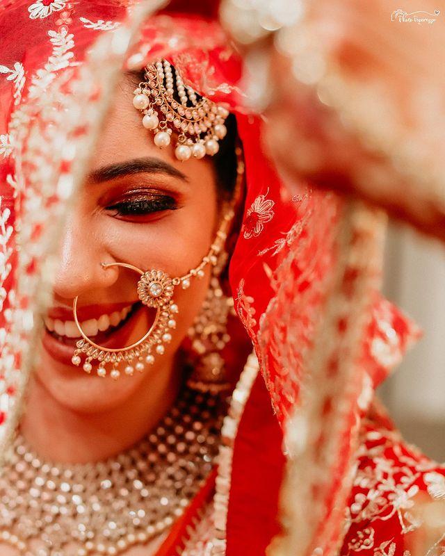 Beautiful bride adorning indian bridal jewellery in a red lehenga
