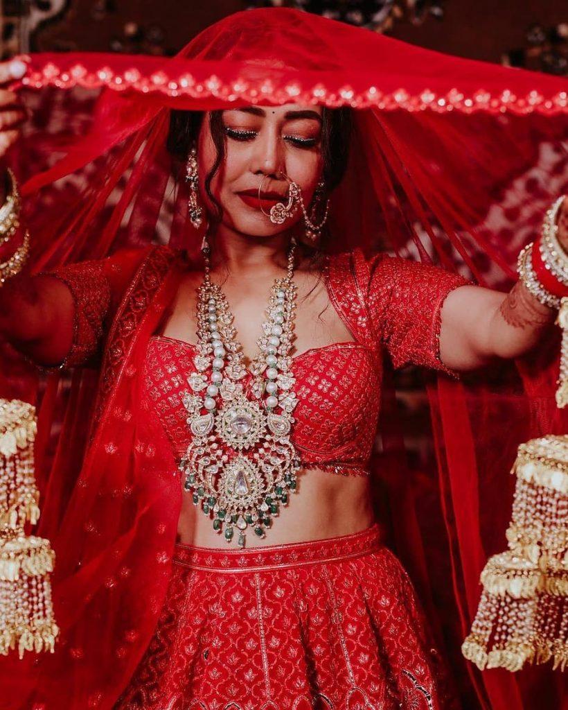 Neha Kakkar wearing a heavy diamond long necklace with sweetheart neckline